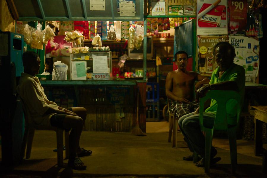 Amigos charlan sentados en el porche de su tienda de alimentación