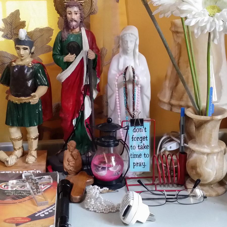 Mesita de noche con virgenes, san jose y estampitas para rezar