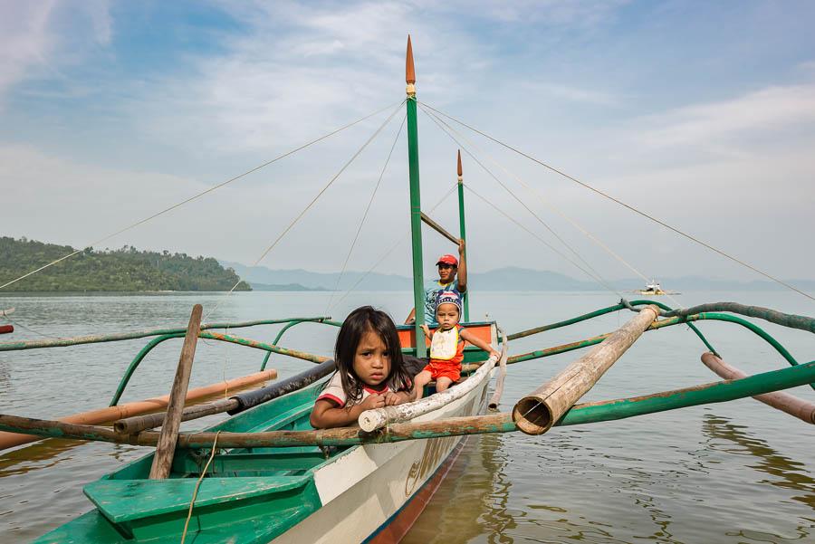 Familia prepara barco para salir a navegar. Port Barton, Filipinas