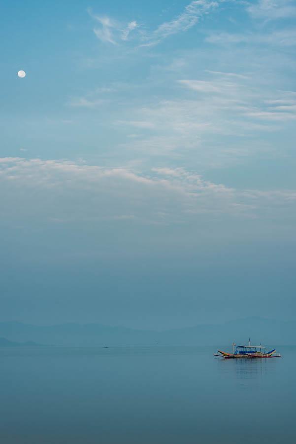 Foto Amanecer Port Barton, encontramos la luna alineada con el barco típico Filipino, la bangka
