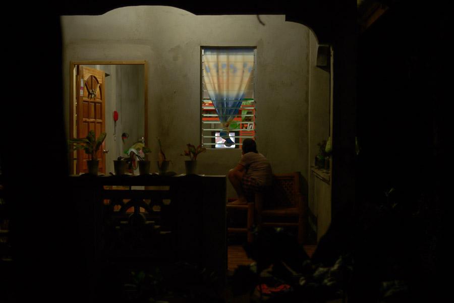 Mujer mira TV en el porche de su casa, Filipinas