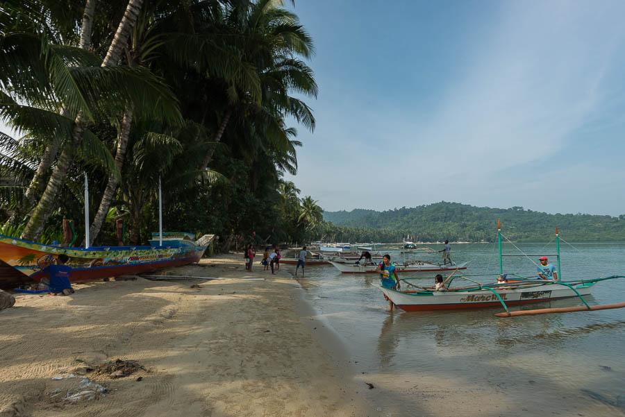 Locales preparando el barco al amanecer para comenzar la jornada. Port Barton. Filipinas