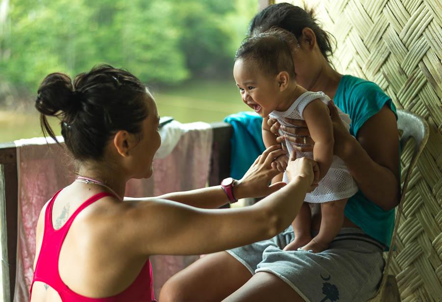 Irene juega con bebe en una casa Filipina donde nos acogieron, Port Barton, Filipinas