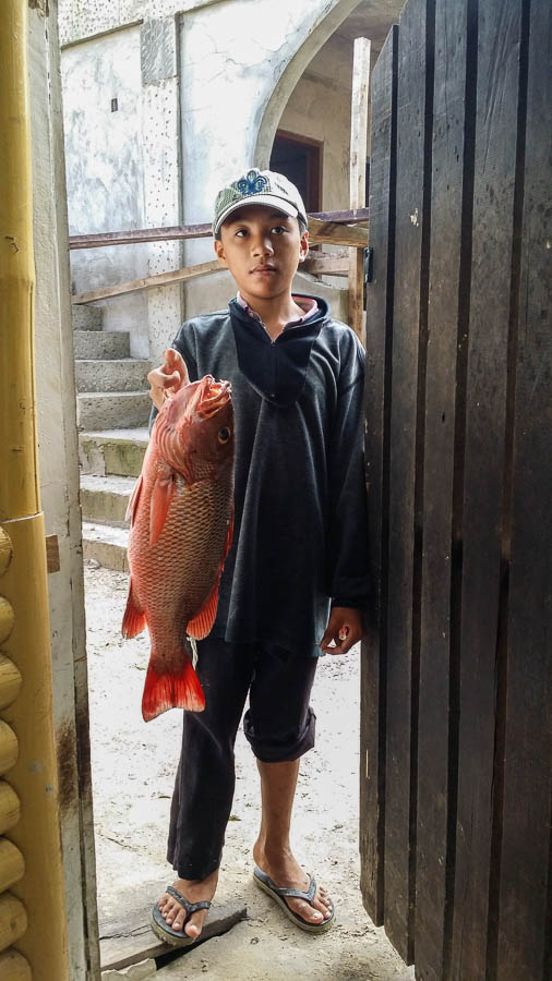 Niño muestra un pez recién pescado. Port Barton, Filipinas