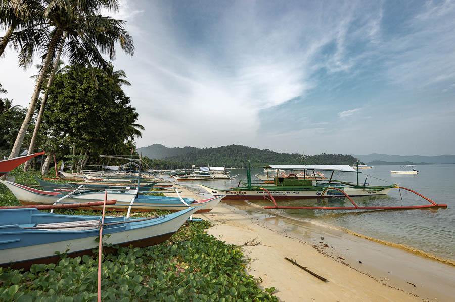 Barcos amarrados en la orilla de la playa de Port Barton, Filipinas